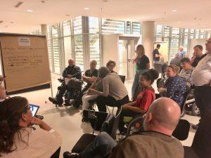 Man sieht viele Teilnehmer*innen die im vor einem Flipchart sitzen und stehen und ein Thema erarbeiten.