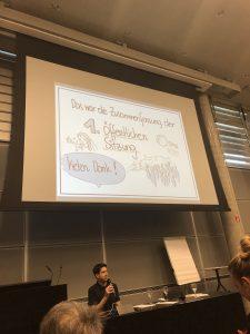 Michael Hanl spricht zum Publikum. Er unterstützte die Veranstaltung mit bildnerischen Zusammenfassungen und einfacher Sprache. © Hannah Wahl