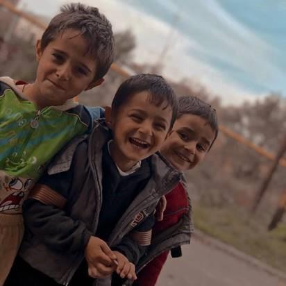 Drei Kinder, die lachen.