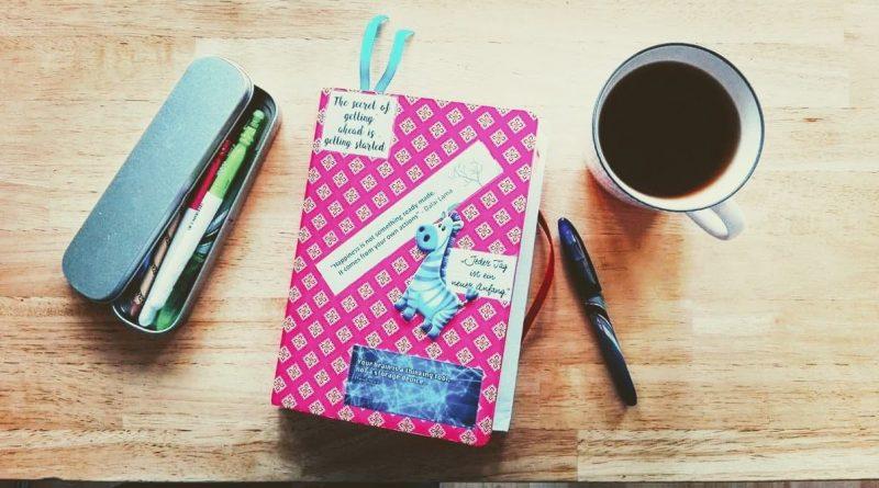 Buch, Stifte und Tasse auf einem Tisch