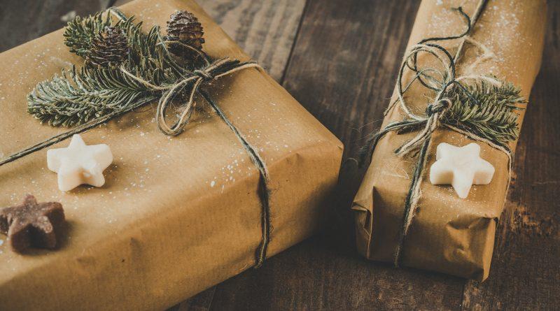 Geschenke in weihnachtlicher Verpackung liegen auf einem Holztisch