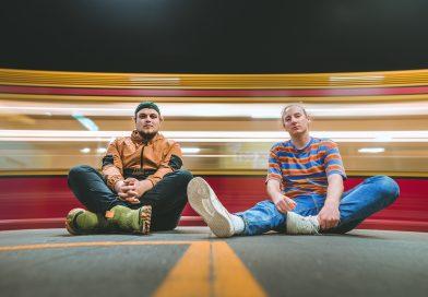 Jonas & Male sitzen am Boden, hinter ihnen sihet man die Lichter einer Bahn.