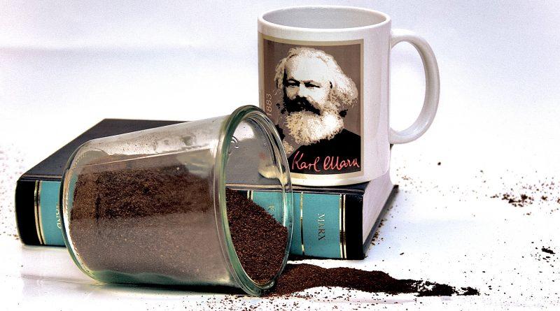 Kaffetasse mit Bild von Karl Marx, davor auslaufendes Kaffepulver