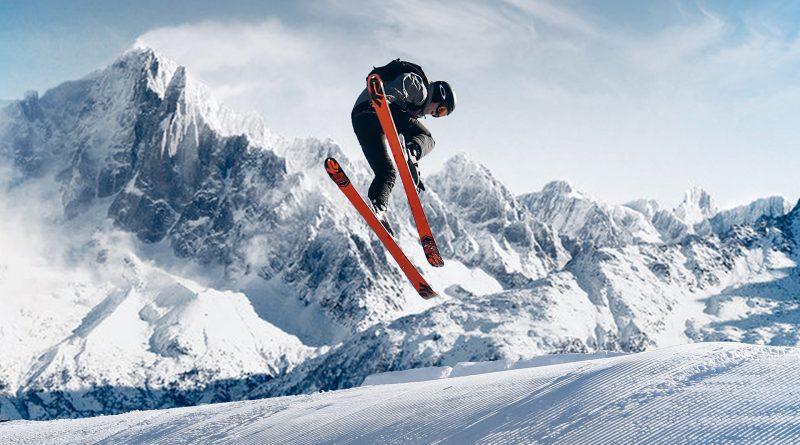 Skifahrer in der Luft, im Hintergrund Berge