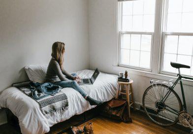 Frau sitzt in Zimmer mit Laptop auf Bett