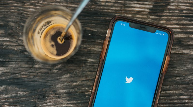 Handy mit Twitter Logo und Kaffeeglas auf einem Holztisch