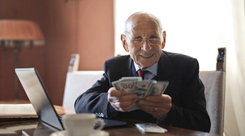 Älterer Mann mit Geldbündel in der Hand