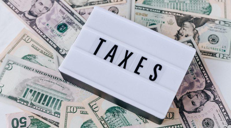"""Schriftzug """"Taxes"""" inmitten von Geldscheinen"""