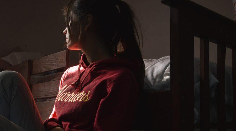"""Frau mit Pullover-Aufschrift """"Warrior"""" sitzt auf dem Boden vor einem Bett"""