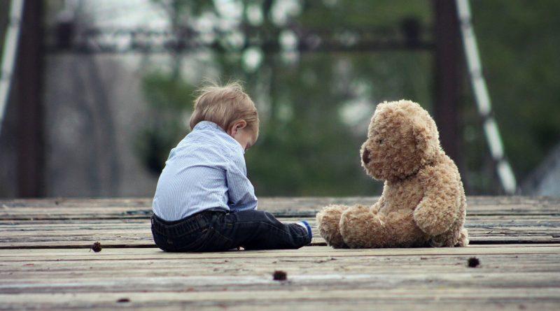 Ein kleines Kind sitzt gegenüber von einem Teddybär auf einer Holzterrasse