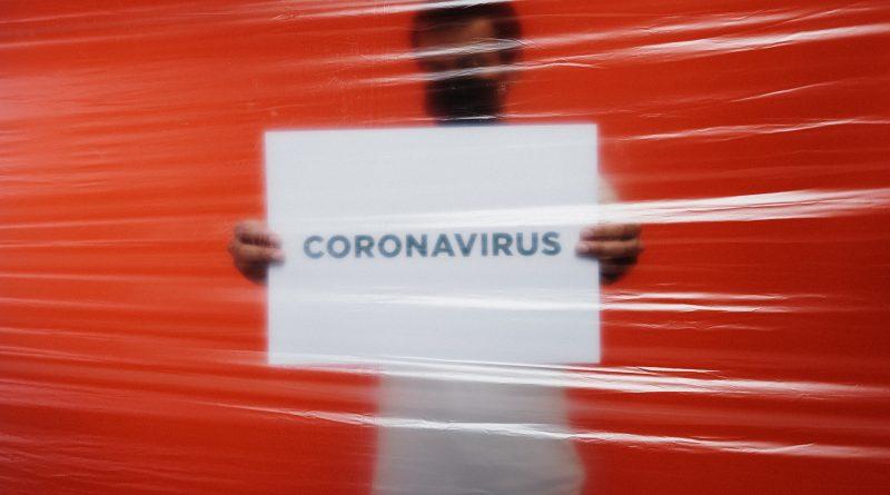 """Mann hält Schild """"Coronavirus"""""""