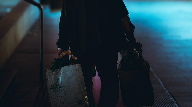 Mensch trägt zwei Taschen, Dunkelheit