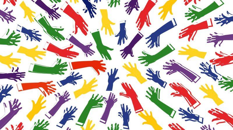 Bunte Hände, die zur Mitte zeigen und eine Einheit bilden