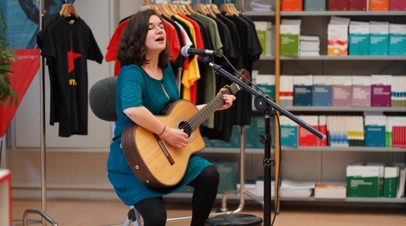Frau spielt Gitarre und singt