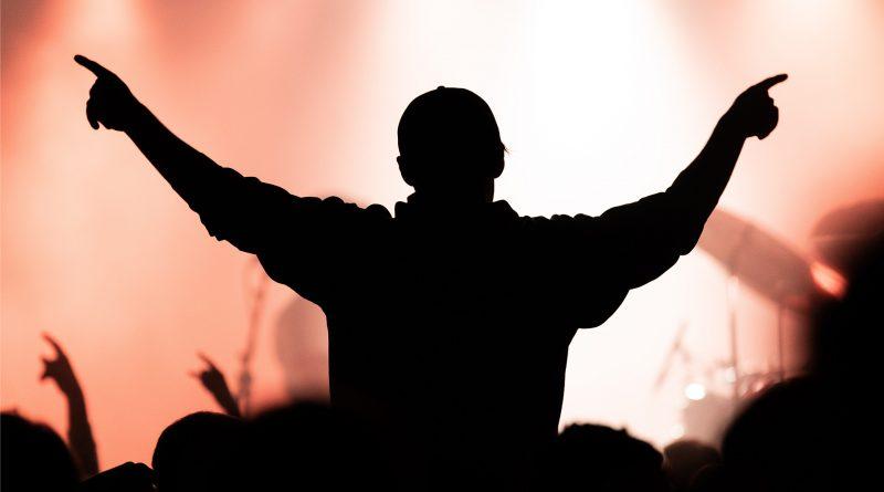 Silhouette eines Menschen bei einem Konzert, streckt die Arme in die Höhe