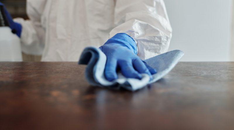 Mensch mit Handschuhen putzt Tisch