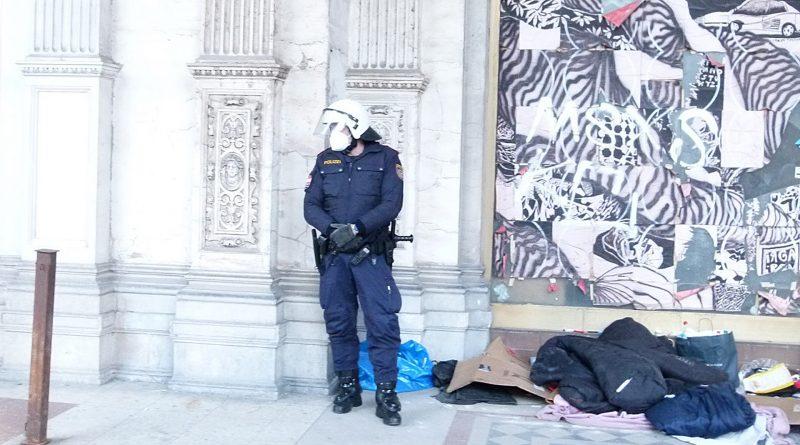 Polizist steht vor einer Häuserwand