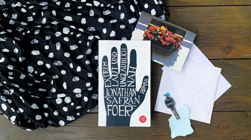 Das Buch liegt auf einem Holztisch, umringt von einem weiß gepunkteten schwarzen Tuch
