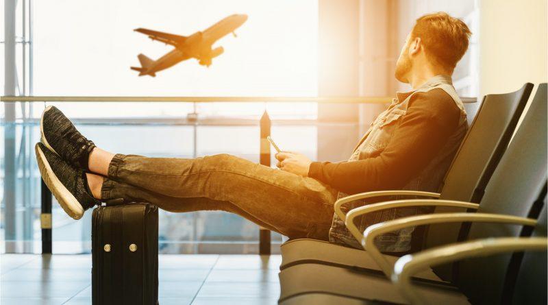Mann sitzt am Flughafen, Füße auf dem Koffer, fliegendes Flugzeug im Hintergrund