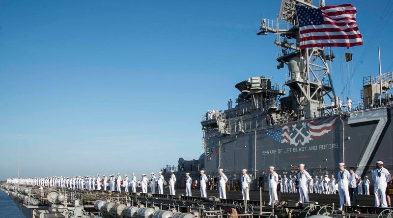Marine-Soladten des US-Armee stehen in einer Linie am Rand eines langen Schiffes