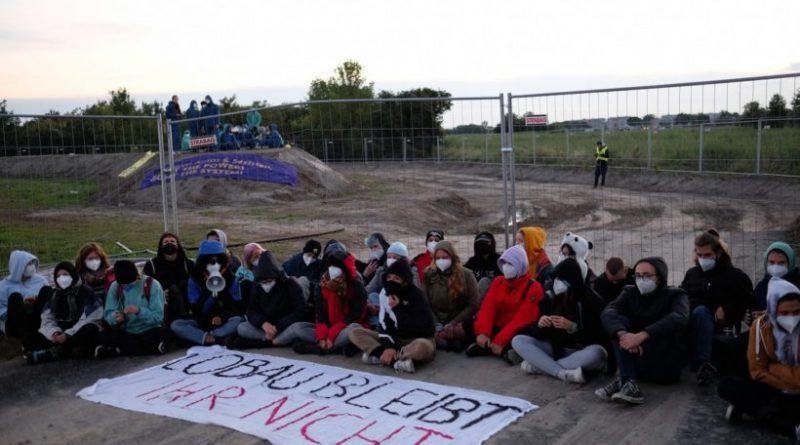 """Junge Menschen sitzen am Boden, davor liegt das Transparent: """"Lobau bleibt, ihr nicht"""""""
