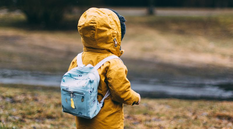 Kind mit gelber Regenjacke und rosa Schulrucksack, von hinten fotografiert