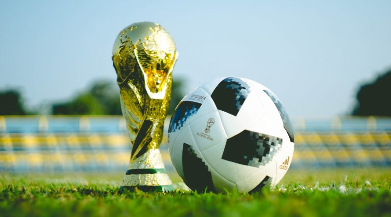 WM-Pokal und schwarz-weißer Fußball auf dem Rasen