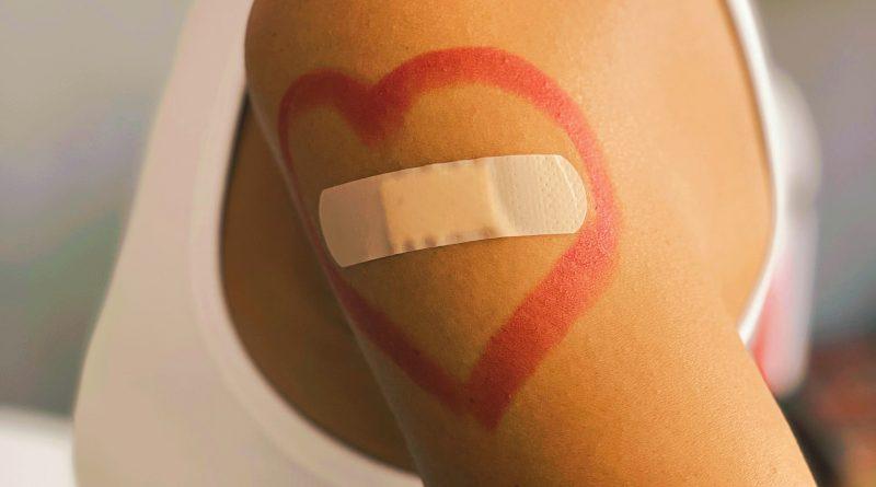 Arm, auf dem ein rotes Herz gemalt ist, in dem ein Pflaster klebt