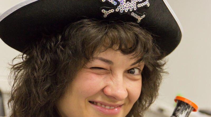 Junge Frau mit Piratenhut zwinkert