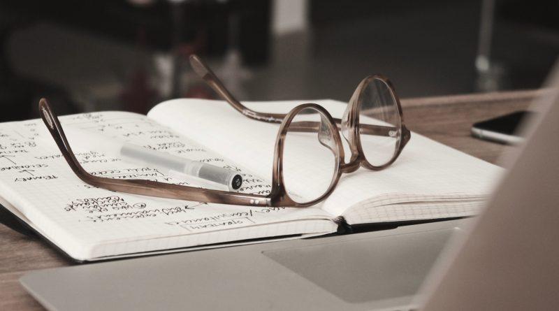 Brille liegt auf einem Notizblock, davor ein Laptop