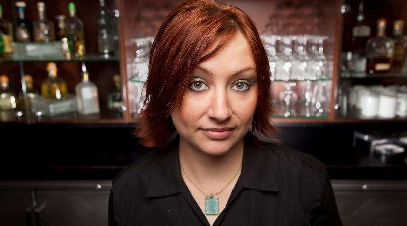 Frau mit schulterlangen Haaren und schwarzem Oberteil steht vor einer Bar