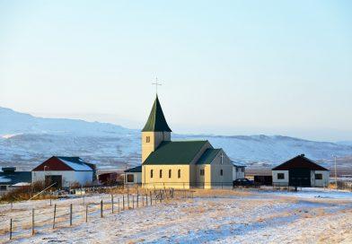 Kirche im Sonnenlicht, daneben kleine Häuser