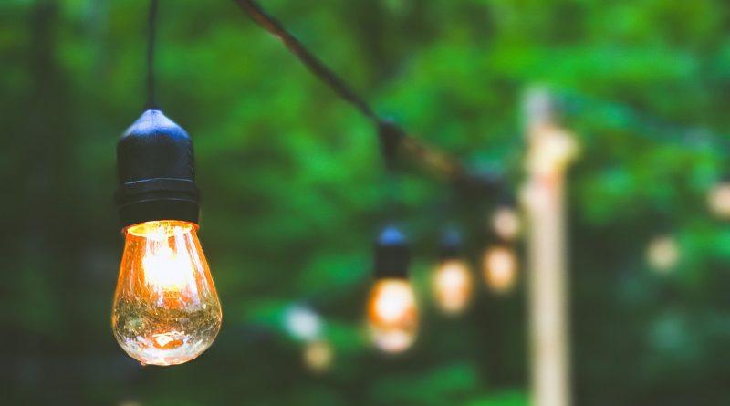 Gelbe Glühbirnen hängen im Freien an einer Leine
