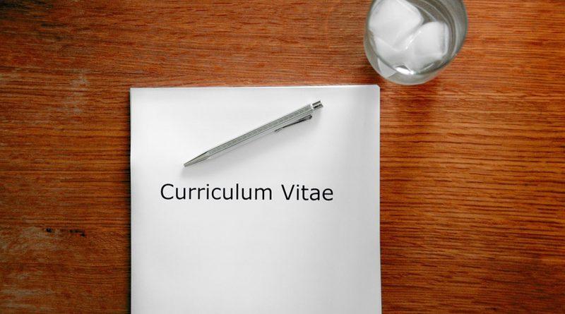 """Zettel mit Aufschrift """"Curriculum Vitae"""" liegt auf einem Holztisch, daneben ein Glas mit Eiswürfeln"""