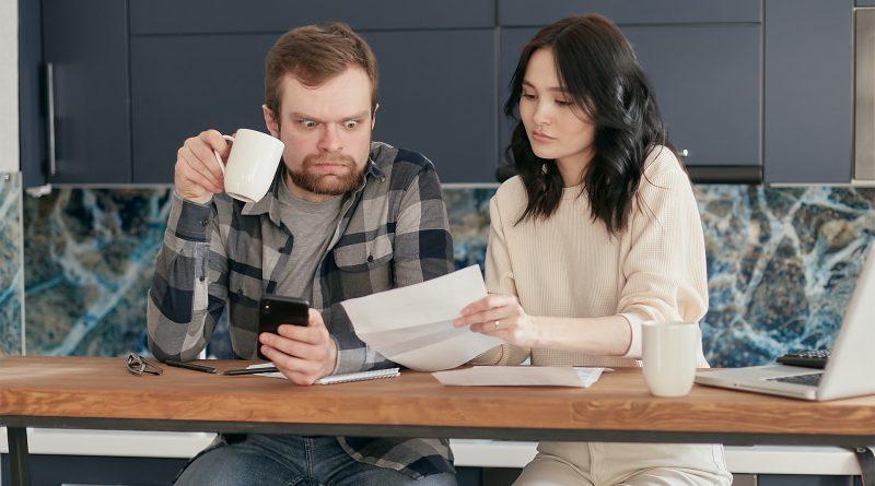 Frau zeigt man Blatt Papier, Mann ist entsetzt