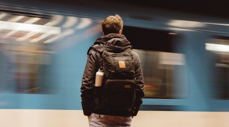 Mensch mit Rucksack steht am Bahnsteig, ein Zug fährt schnell vorbei